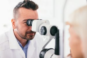 Accent Eye Care optician-checking-his-patients-eyes-UXNERY8